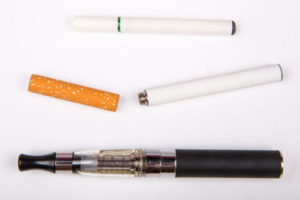 The image shows different types of electronic cigarettes against a plain background