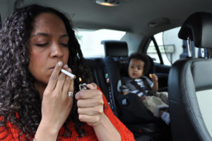 Photo shows an adult woman smoking in a car containing children